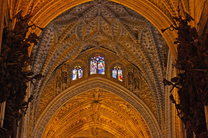 A gothic looking interior wall flanked by sculptures of trumpeting angels.