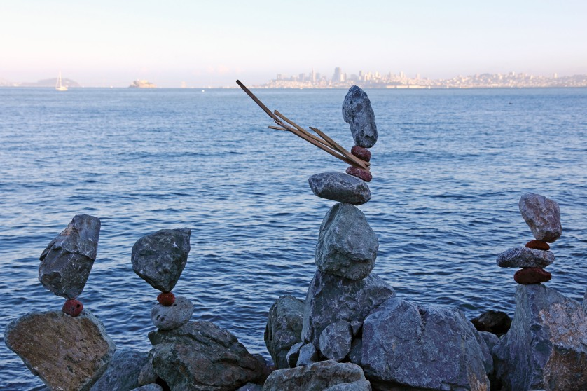 Rock balancing along the coast of Sausalito, with the SF skyline in the background